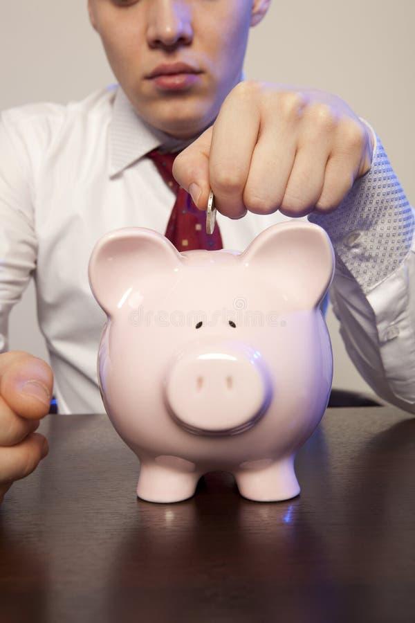 Biznesmen z różowym prosiątko bankiem obrazy stock