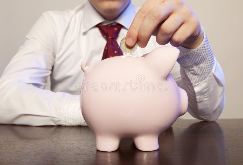 Biznesmen z różowym prosiątko bankiem zdjęcie stock