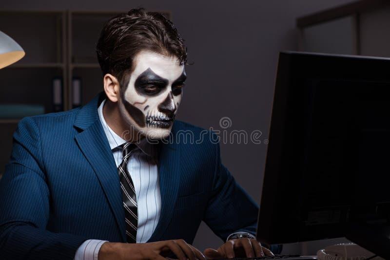 Biznesmen z straszną twarzy maską pracuje póżno w biurze fotografia stock