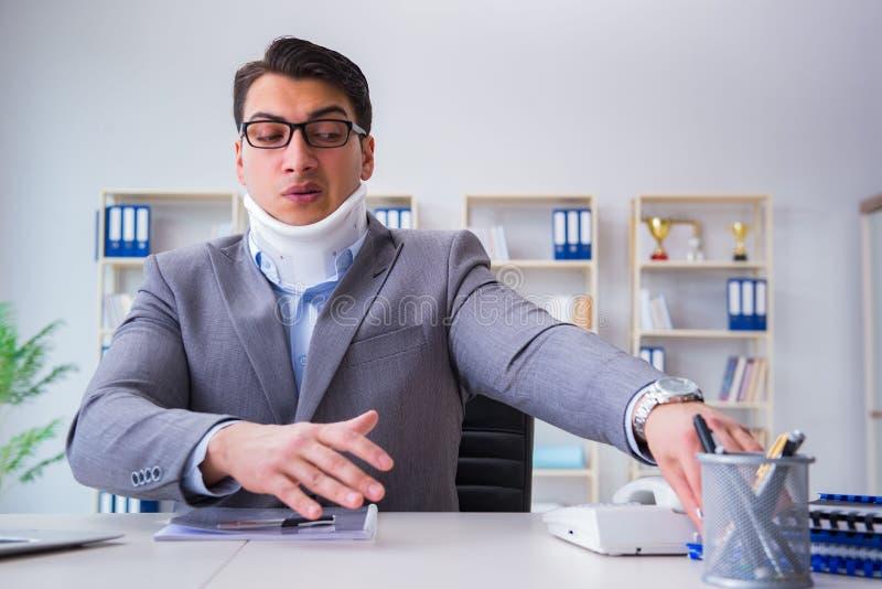 Biznesmen z szyja urazem pracuje w biurze obrazy royalty free