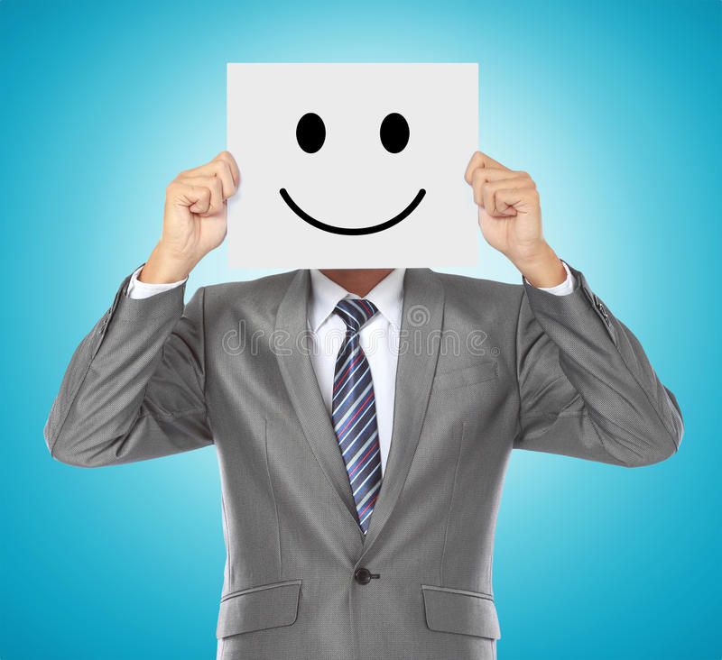 Biznesmen z uśmiechniętą maską fotografia stock