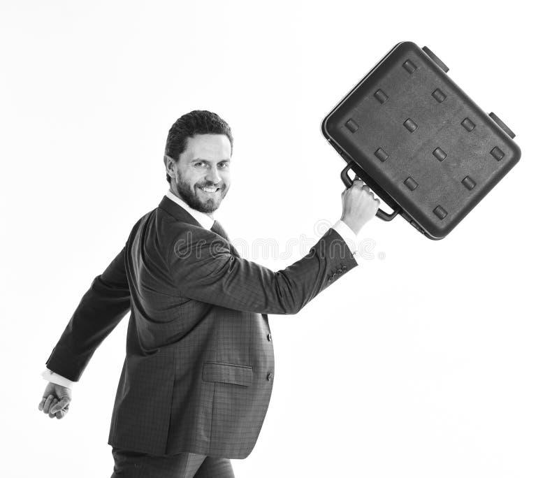 Biznesmen z uśmiechniętą twarzą w ruchu naprzód Mężczyzna w błękitnym formalnym kostiumu trzyma czarną skrzynkę i chodzi fotografia royalty free