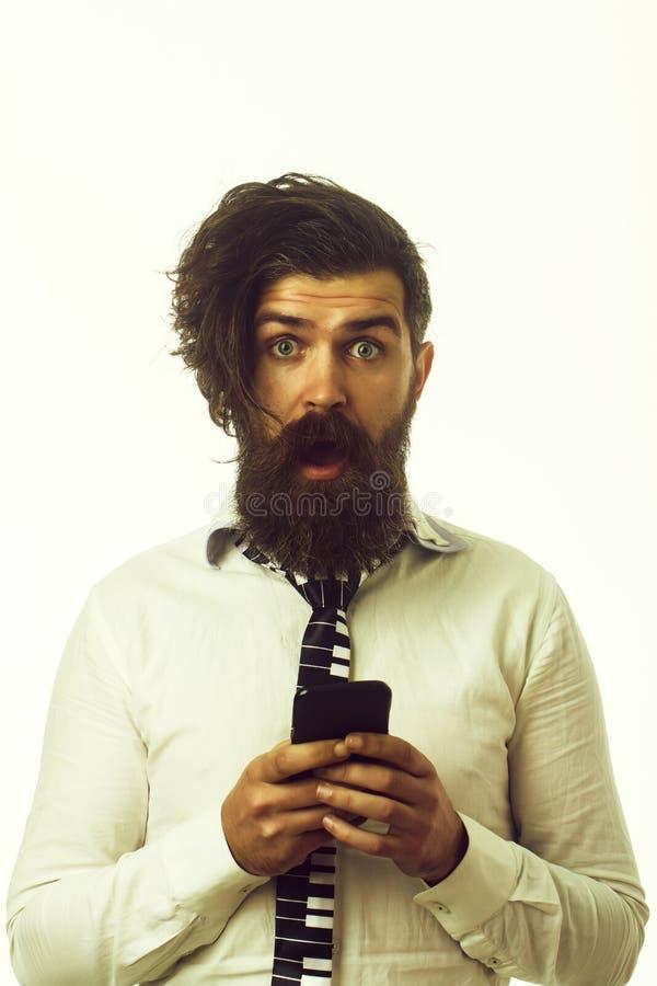 Biznesmen z zdziwionym twarz chwyta telefonem kom?rkowym zdjęcia royalty free