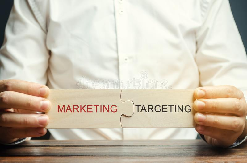 Biznesmen zbiera łamigłówki z słowo marketingiem - Celujący Biznesowi narz?dzia Reklamowi mechanizmy Ulepszać wydajność fotografia stock
