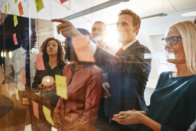 Biznesmena brainstorming z jego różnorodnym personelem na szklanej ścianie zdjęcia royalty free