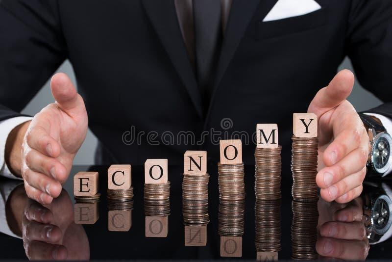 Biznesmena chronienia gospodarki bloki na brogować monetach fotografia royalty free
