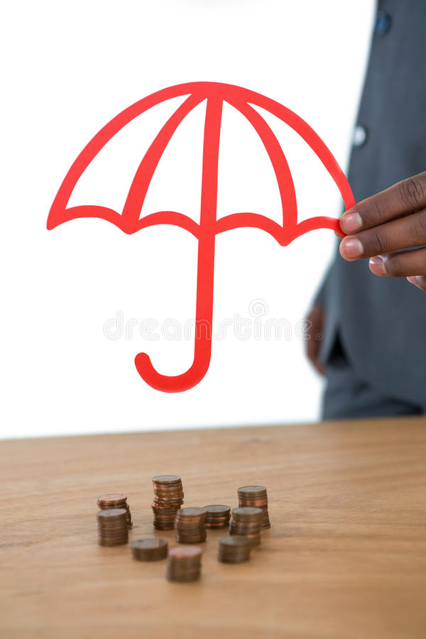 Biznesmena chronienia sterta monety z parasolem przy biurkiem obrazy stock