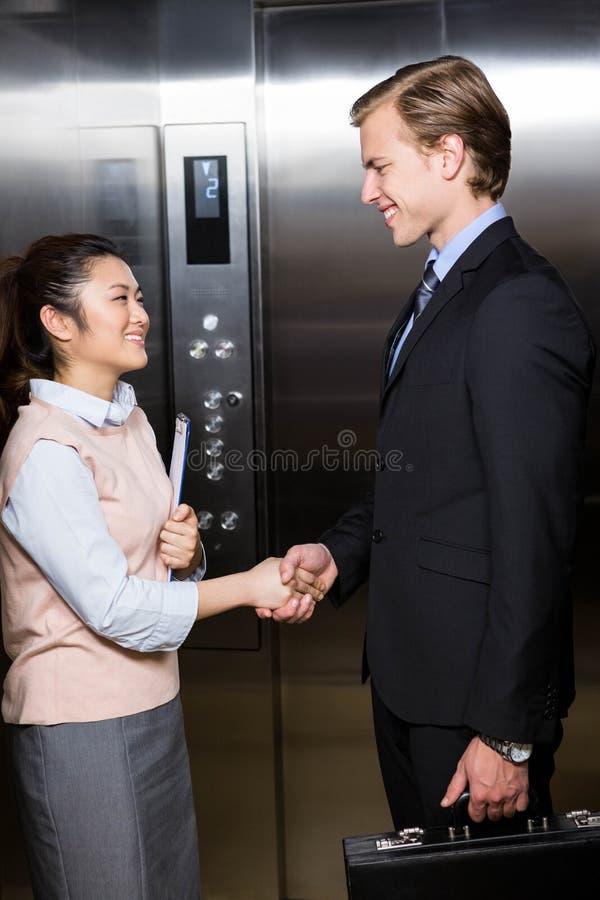 Biznesmena chwiania ręki z bizneswomanem w windzie zdjęcie royalty free