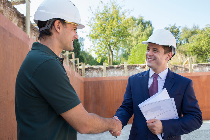 Biznesmena chwiania ręki Z budowniczym Na budowie zdjęcia stock