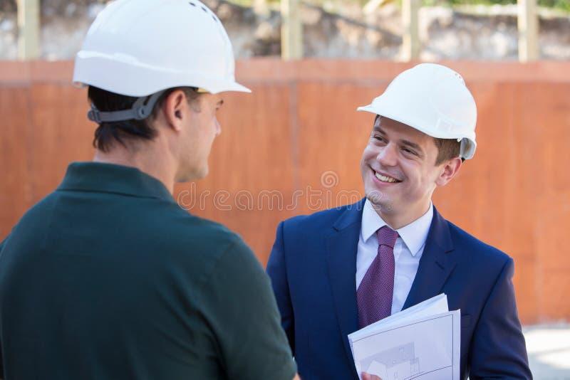 Biznesmena chwiania ręki Z budowniczym Na budowie obraz royalty free