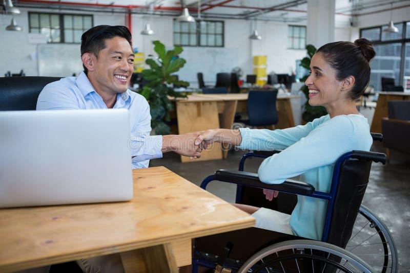 Biznesmena chwiania ręki z niepełnosprawnym kolegą obrazy royalty free