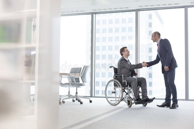 Biznesmena chwiania ręki z uśmiechać się niepełnosprawnego kolegi w sala posiedzeń przy biurem fotografia stock