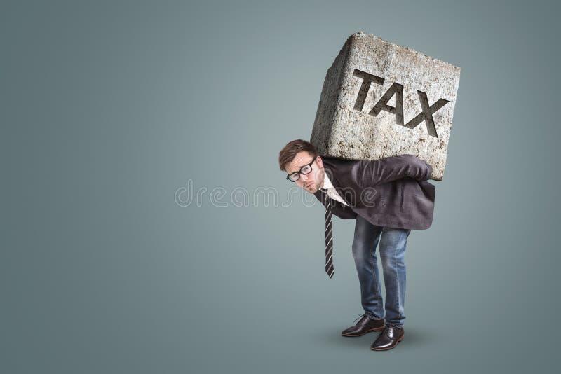 Biznesmena chylenie pod ciężkim kamieniem z słowem podatek na nim zdjęcie stock