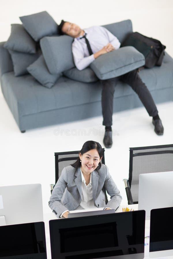 Biznesmena dosypianie na kanapie w godzinach pracujących podczas gdy biznesowy wom fotografia royalty free