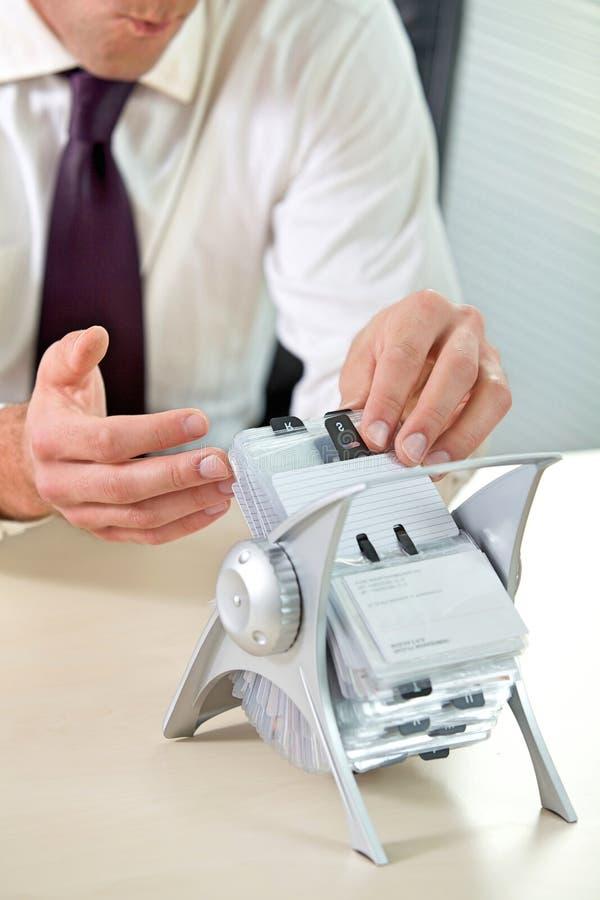 Biznesmena gmerania wizytówka od stojaka zdjęcie stock