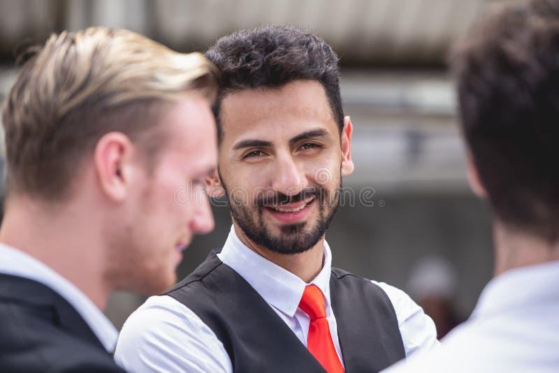 Biznesmena latynoskiego uśmiechu przyglądająca kamera gdy opowiadający z partnerem szczęśliwym obraz royalty free