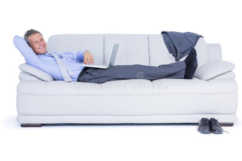 Biznesmena lying on the beach na kanapie używać jego laptop ono uśmiecha się przy kamerą obrazy royalty free