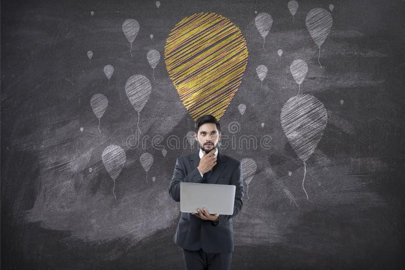 Biznesmena mienia laptop przed blackboard z balonem obrazy royalty free