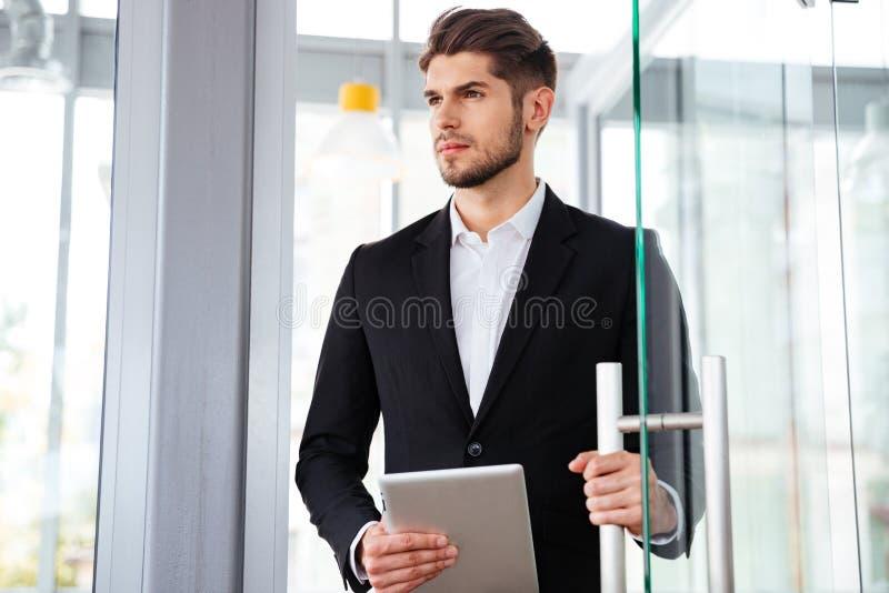Biznesmena mienia pastylka i wchodzić do drzwi w biurze obrazy royalty free