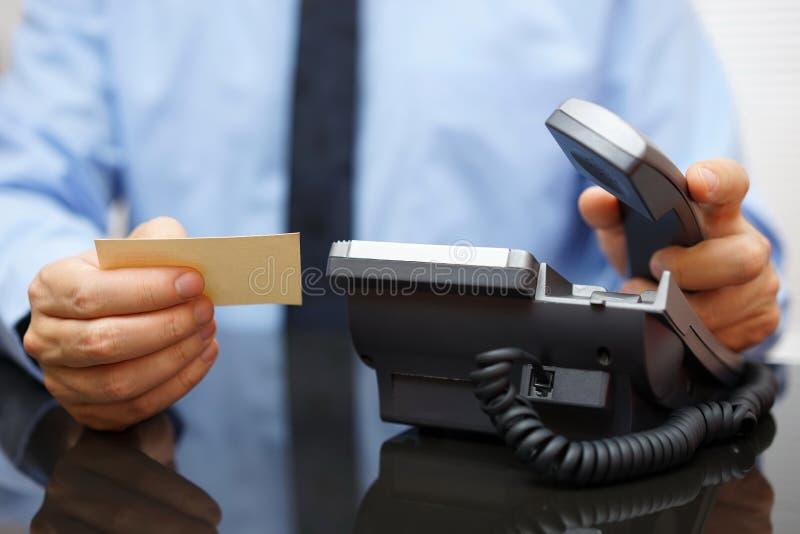 Biznesmena mienia wizytówka i dzwonić jego klienta obrazy stock