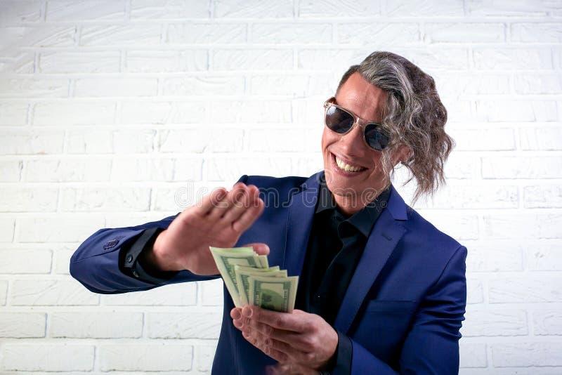 Biznesmena miotania pieni?dze na bia?ym tle M??czyzna w kostium odzie?y marnowania pieni?dze, miotanie banknoty, dolary obraz royalty free