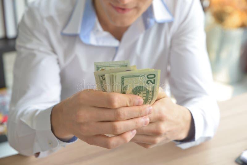 Biznesmena obsiadanie na biurka i mienia pieniądze zdjęcie royalty free