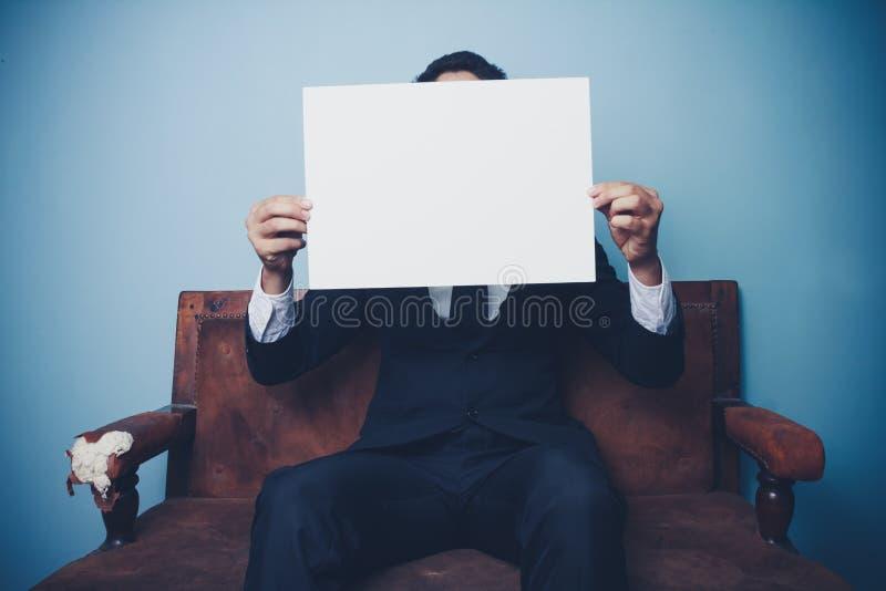 Biznesmena obsiadanie na kanapy mienia bielu pustym znaku zdjęcia stock