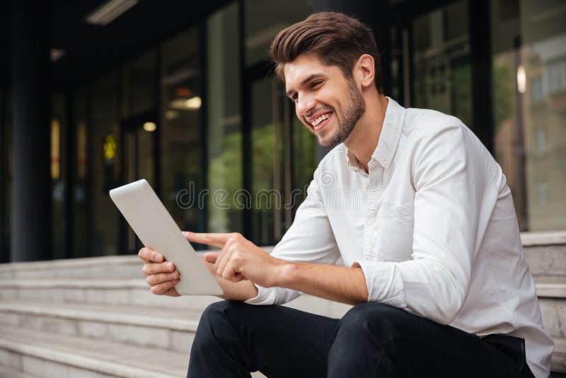Biznesmena obsiadanie na schodkach i używać outdoors pastylce obraz stock