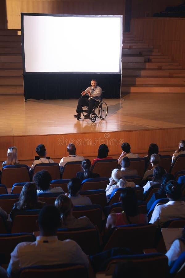 Biznesmena obsiadanie na wózku inwalidzkim i dawać widownia prezentacja obraz royalty free