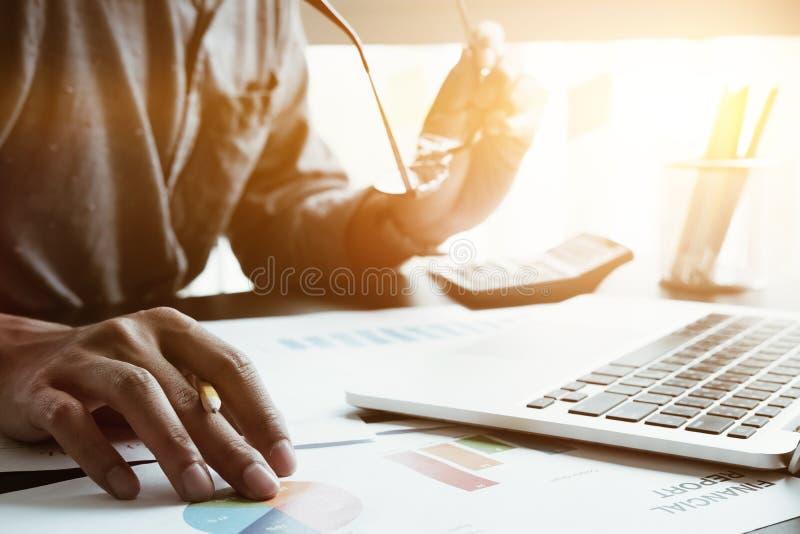 Biznesmena obsiadanie przy jego biurem trzyma glas używać laptopem i, zdjęcie royalty free
