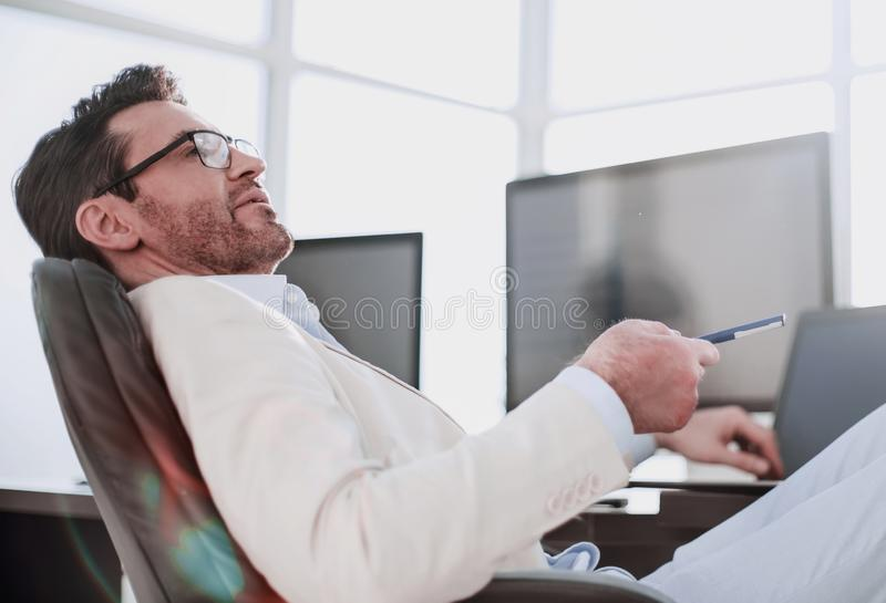 Biznesmena obsiadanie przy jego biurkiem podczas pracuj?cej przerwy obraz royalty free