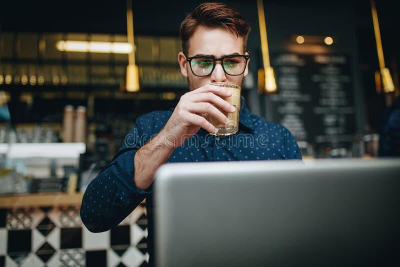 Biznesmena obsiadanie przy restauracyjnym działaniem na laptopie zdjęcia royalty free