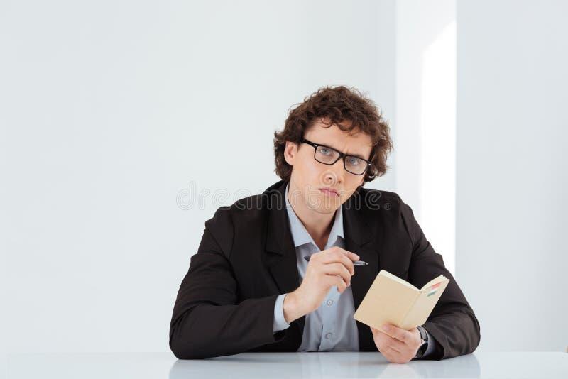 Biznesmena obsiadanie przy stołem z piórem i notatnikiem zdjęcie royalty free
