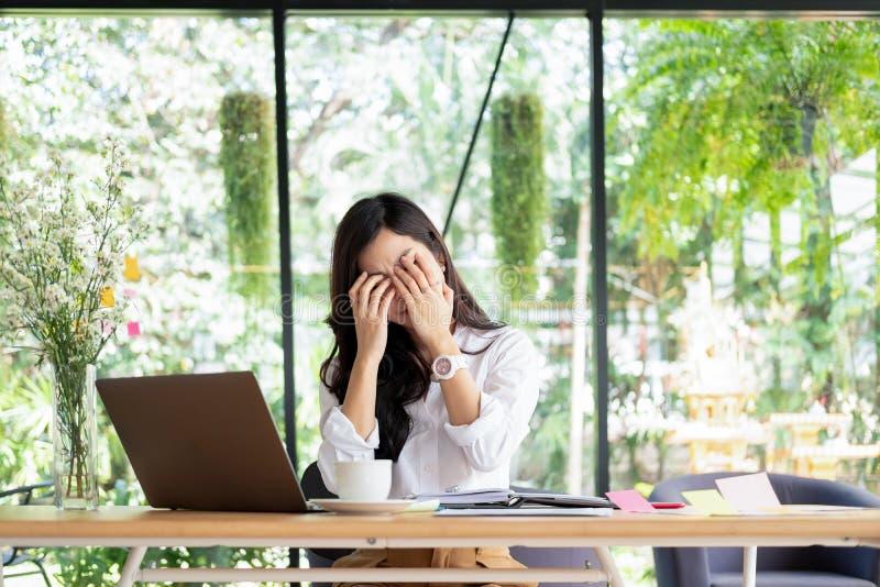 Biznesmena odczucia ból w ich oczach podczas gdy pracujący w biurowym, medycznym pojęciu, fotografia stock