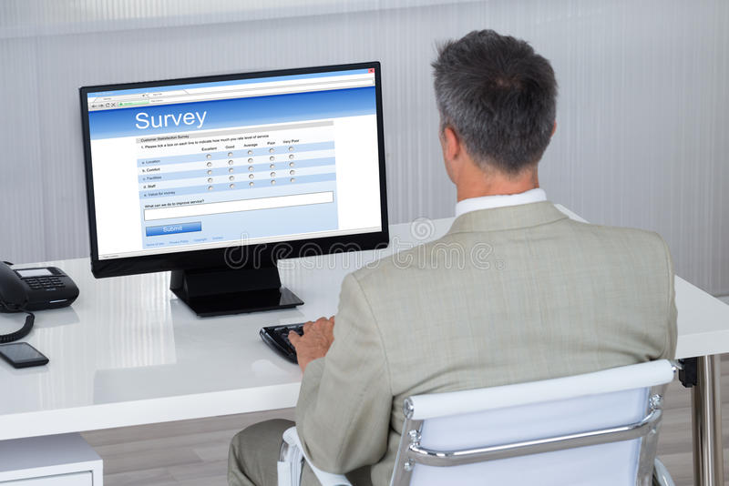 Biznesmena plombowania ankiety forma Na komputerze Przy biurkiem zdjęcia royalty free