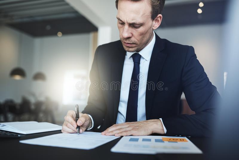 Biznesmena podpisywania dokumenty podczas gdy siedzący przy jego biurowym biurkiem fotografia stock