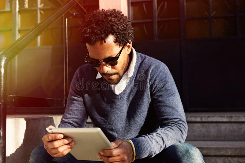 Biznesmena podróżować, pracuje w Nowy Jork Młody murzyn jest usytuowanym na ulicie, czytanie, pracuje na urządzeniu elektroniczny zdjęcie royalty free