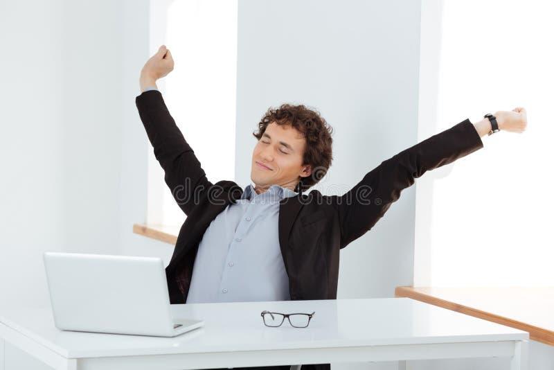 Biznesmena rozciągania ręki przy jego miejscem pracy zdjęcie stock