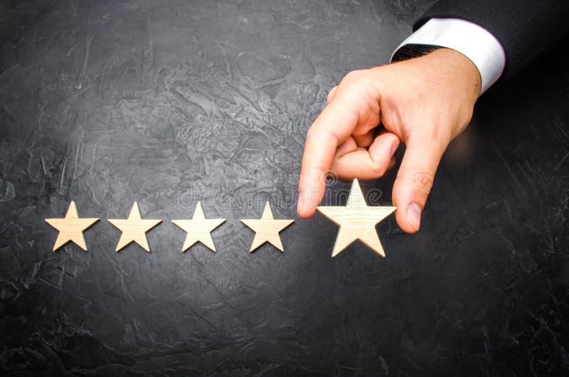 Biznesmena ` s ręka w kostiumu trzyma kwinty gwiazdę Dostaje kwinty gwiazdę Pojęcie ocena hotele i restauracje, zdjęcia royalty free