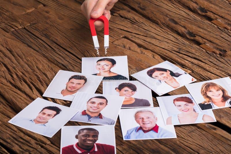 Biznesmena ` s ręka Z podkowa magnesem Przyciąga ludzi zdjęcie stock
