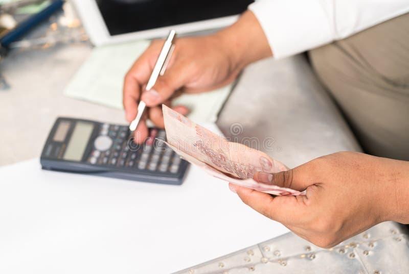 Biznesmena ` s wręcza mienie kalkulatora i banknoty obrazy stock