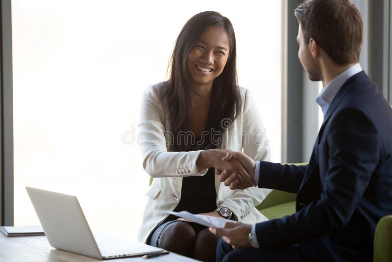 Biznesmena uścisku dłoni uśmiechniętego Azjatyckiego klienta końcowa transakcja biznesowa obraz stock