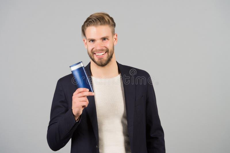 Biznesmena uśmiech z szamponu lub gel butelką w ręce, zdrój Mężczyzna z eleganckim włosy, ostrzyżenie, salon Mężczyzna higiena, p zdjęcia stock