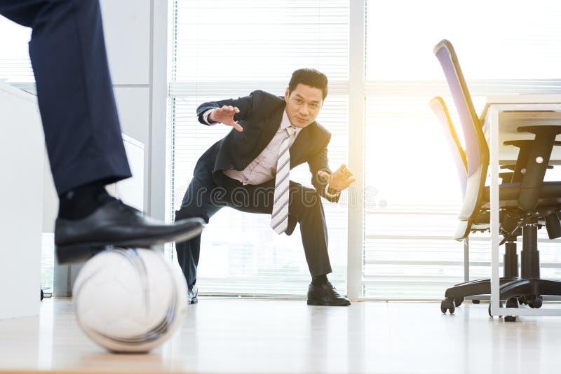 Biznesmeni bawić się futbol w biurze zdjęcie royalty free