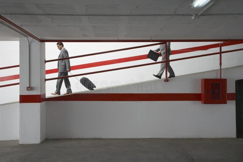 Biznesmeni Chodzi W dół rampę Z bagażem W garażu zdjęcie stock