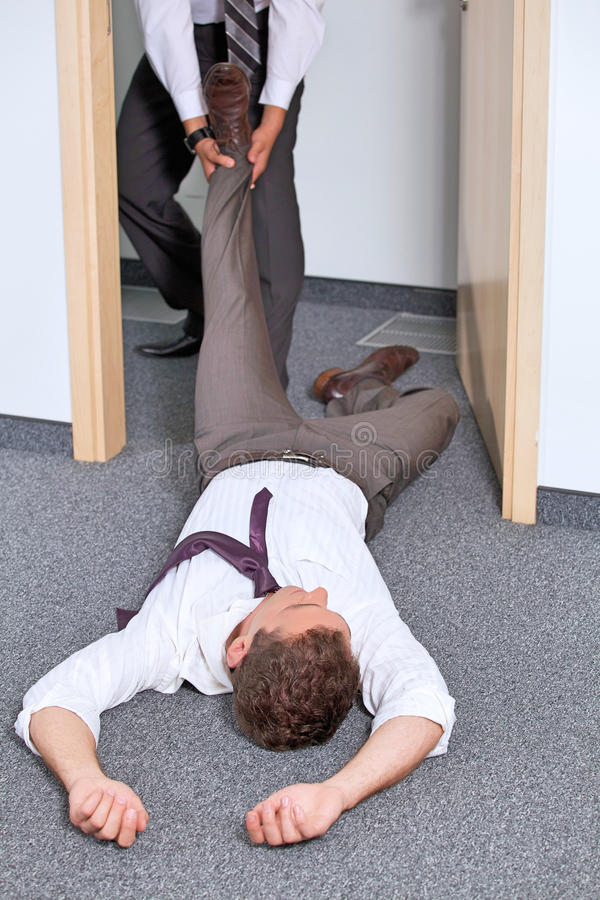 Biznesmeni ciągnie kolega nogę przy biurem zdjęcia royalty free