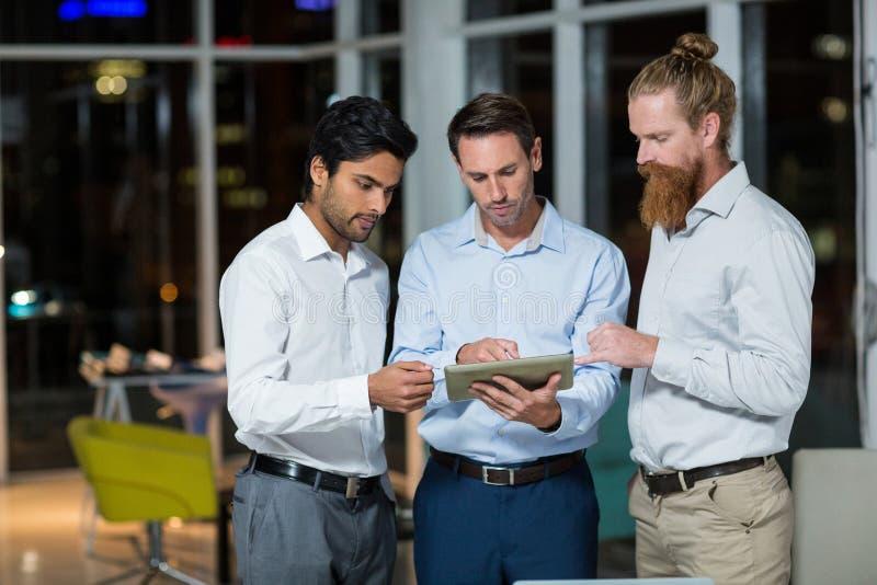 Biznesmeni dyskutuje nad cyfrową pastylką fotografia royalty free