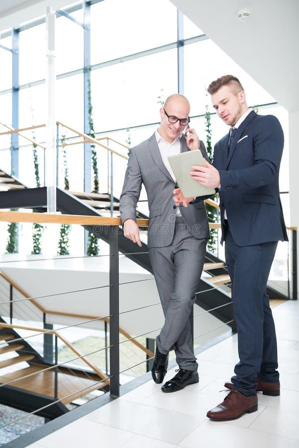 Biznesmeni dyskutuje nad cyfrową pastylką w biurze obraz royalty free