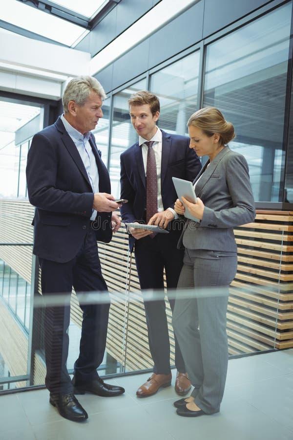 Biznesmeni dyskutuje nad urządzeniami elektronicznymi w przejściu zdjęcie royalty free