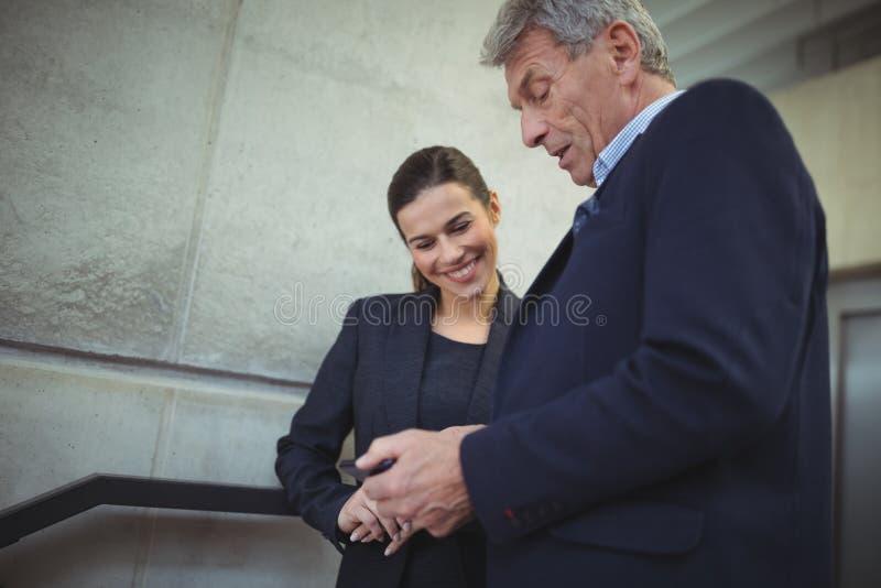 Biznesmeni dyskutuje nad urządzeniem elektronicznym w korytarzu zdjęcie stock